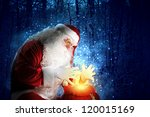 Santa with beard and red hat holding and looking into the sack - stock photo