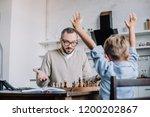 triumphing little son raising... | Shutterstock . vector #1200202867