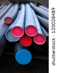 Stack of plastic black pipes with colorful ends - stock photo