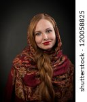 Portrait of looking at camera and smiling Slavonic girl with red braided hair, dark background - stock photo