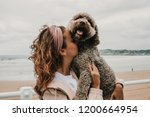 Stock photo  young woman wearing a pink coat playing with her adorable brown spanish water dog on the seafront 1200664954