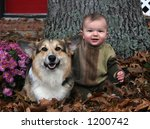 baby boy and dog sitting in leaves - stock photo