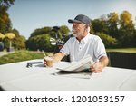 smiling senior man sitting at a ... | Shutterstock . vector #1201053157