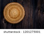 Small photo of Round wicker basket on wooden uncouth Board, rustic background, top view, copy space