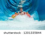 Small photo of Boy having fun on the water slide on floater in the aqua fun park.