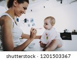 baby having breakfast and being ... | Shutterstock . vector #1201503367