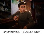 young man drinking beer at the... | Shutterstock . vector #1201644304