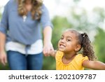 cute lille girls holding her... | Shutterstock . vector #1202109787