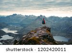 Adventurous man is standing on top of the mountain and enjoying the beautiful view during a vibrant sunset. Beautiful Nature Norway natural landscape aerial photography