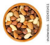 nuts and raisins in wooden bowl.... | Shutterstock . vector #1202431411