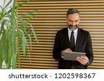 handsome middle age businessman ... | Shutterstock . vector #1202598367