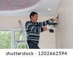 worker installs the indoor unit ... | Shutterstock . vector #1202662594