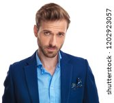 Small photo of handsome young smart casual man with a smug look posing on white background