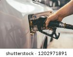 man fueling up the car in the... | Shutterstock . vector #1202971891