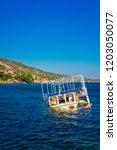 semi sunken boat on the shore...   Shutterstock . vector #1203050077