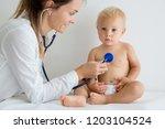 pediatrician examining baby boy.... | Shutterstock . vector #1203104524