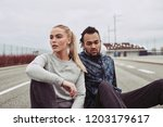 diverse young couple sitting on ... | Shutterstock . vector #1203179617