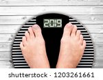 2019 feet on a weight scale on... | Shutterstock . vector #1203261661