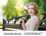 young beautiful woman walks... | Shutterstock . vector #1203398617