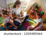 preschool teacher reading a... | Shutterstock . vector #1203485464
