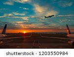 Small photo of Plane taking off at sunrise at Boston Logan international airport with symmetry and gorgeous vibrant cloudy sky blue and orange going on vacation travel adventure