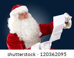 Santa Claus holding and reading a letter to him - stock photo