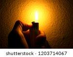 hand holding lighter in the...   Shutterstock . vector #1203714067