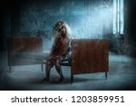 scary little girl sitting on a... | Shutterstock . vector #1203859951