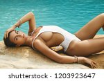sexy woman in white swimsuit is ...   Shutterstock . vector #1203923647