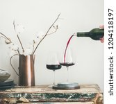 red wine pouring from bottle in ... | Shutterstock . vector #1204118197
