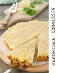 tart with cabbage and cheese on a wooden cutting board, cut piece - stock photo