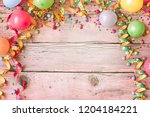 Small photo of Carnival background with balloons and streamers forming a border around rustic pink tinged wood with copy space