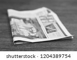 single newspaper on wooden... | Shutterstock . vector #1204389754