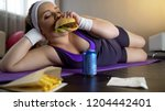 obese female eating greasy... | Shutterstock . vector #1204442401