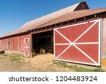 old wooden red barn on rural... | Shutterstock . vector #1204483924