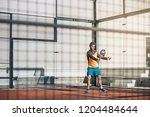 man playing padel in a orange... | Shutterstock . vector #1204484644
