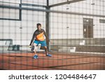 man playing padel in a orange... | Shutterstock . vector #1204484647