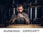 Stock photo portrait of a pensive tattooed hipster male with stylish beard and hair in the shirt in indie 1204514377