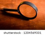 magnifying glass on a wooden...   Shutterstock . vector #1204569331
