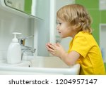 child boy washing his face in... | Shutterstock . vector #1204957147