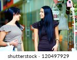 two beautiful smiling women walking the mall and talking - stock photo
