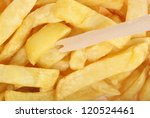 Potato chips in takeaway carton with wooden chip fork. - stock photo