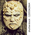 Small photo of Monster face with white eyes, sharp thorns and warts. Man with dragon skin and beard. Alien or reptilian makeup. Demon head on grey knitted background. Horror and fantasy concept.