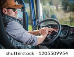 Caucasian Truck Driver in His 30s in the Semi Cabin. Modern Transportation Job. - stock photo