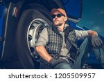 Relaxed Caucasian Truck Driver Seating on the Ground and Support His Back on the Semi Truck Wheel. - stock photo