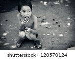 Stock photo lone hungry boy eats sitting on the ground 120570124