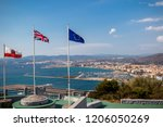 Gibraltar, United Kingdom, 1st October 2018:- View from the top of the Rock  into Spain, with the flags of Gibraltar, UK and EU flying. Gibraltar is a British Overseas Territory. - stock photo