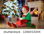 child opening present at... | Shutterstock . vector #1206513244