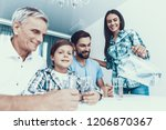 smiling mother pouring water in ... | Shutterstock . vector #1206870367