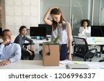 Small photo of Upset female employee packing belongings in box, frustrated stressed girl getting fired from job ready to leave on last day at work, sad office worker desperate about unfair dismissal losing job